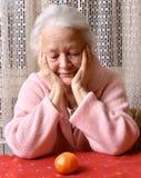 看蜜桔的老妇人 免版税图库摄影