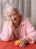 看蜜桔的老妇人 免版税库存图片