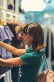 看衣裳的一个愉快的少妇的半身体射击垂悬在衣物商店里面的路轨巴厘岛的 库存照片