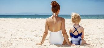 看见从后面母亲和孩子坐在海滩的泳装的 免版税库存图片