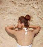 看见从放置在沙子的泳装的后面妇女 图库摄影