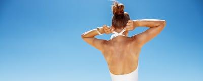 看见从栓白色泳装的后面妇女在沙滩 免版税库存照片