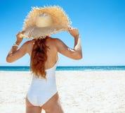 看见从白色泳装和草帽的后面妇女在海滩 免版税库存图片