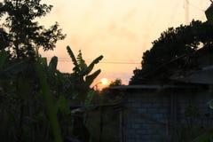 看见在村庄房子后的太阳落山 免版税库存照片