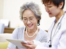 看见家庭医生的资深亚裔妇女 免版税图库摄影