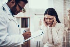 看见患者的印度医生在办公室 医生听妇女的症状 妇女的头疼 免版税库存照片
