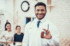 看见患者的印度医生在办公室 医生摆在用与母亲和女儿的糖浆在背景中 免版税库存照片