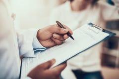 看见患者的印度医生在办公室 医生采取关于妇女的症状的笔记 免版税库存照片