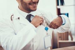 看见患者的印度医生在办公室 母亲给金钱医治 医生在口袋投入金钱 免版税库存照片