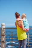 看见从后面健身母亲和孩子堤防的 免版税库存照片