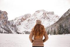 看见从后面妇女户外在积雪覆盖的山中 免版税库存照片