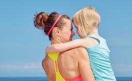 看见从后面拥抱在堤防的健身母亲和孩子 免版税库存照片