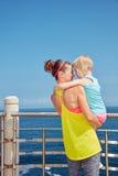 看见从后面拥抱在堤防的健身母亲和孩子 库存图片