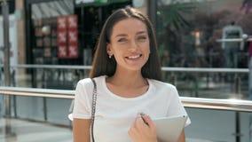 看触摸板屏幕的年轻女实业家半身画象,当站立在现代办公室空间内部时 免版税库存图片