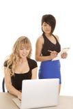 看计算机一微笑的两名妇女 免版税库存图片