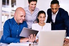 看计算机和片剂的小组不同的企业家 库存照片