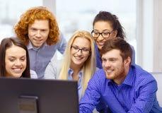 看计算机显示器的微笑的企业队 免版税库存照片