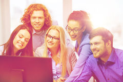 看计算机显示器的微笑的企业队 免版税库存图片