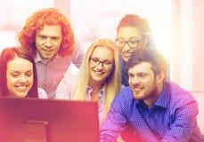 看计算机显示器的微笑的企业队 免版税图库摄影