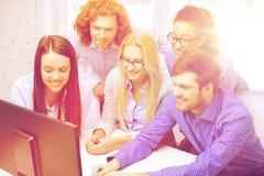 看计算机显示器的微笑的企业队 库存图片