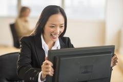 看计算机显示器的愉快的女实业家在办公室 库存图片