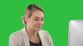 看计算机的成人女实业家在一个绿色屏幕上的办公室,色度钥匙 股票录像