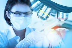 看试管的年轻科学家在实验室里 免版税库存图片