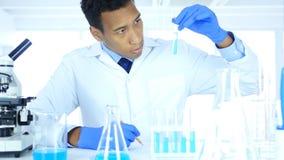 看试管蓝色解答和使用显微镜的科学家在实验室 免版税库存图片