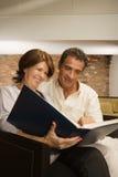 看象册的成熟夫妇 免版税图库摄影