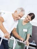 看资深患者的护士使用步行者在康复中心 免版税图库摄影