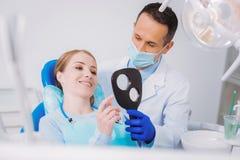 看起来一个牙齿诊所的微笑的患者敬佩她括号和高兴 库存照片
