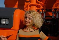看起来一名微笑的年轻金发妇女的画象,站立在橙色履带牵引装置挖掘机附近和愉快 库存图片