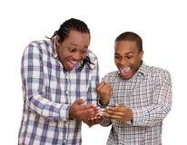 看起来两个的人在智能手机的激动的,观看的橄榄球赛 免版税库存图片
