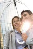 看起来企业的夫妇去,当站立在伞下在晴天时 免版税库存图片