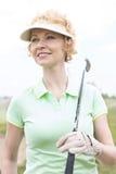 看起来体贴的中年的妇女去,当拿着高尔夫俱乐部时 库存图片