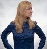 看起来偶然蓝色的衬衣的好奇年轻女人正确 免版税库存照片