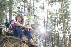 看起来全长微笑的男性的远足者去,当坐峭壁在森林里时 免版税库存照片