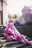 看起来公主的美丽的深色头发的女孩,长的晚礼服桃红色的 库存图片