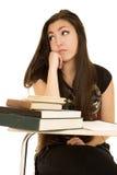 看起来分散的看的学校书桌的逗人喜爱的女孩  库存图片