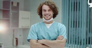 看起来医院年轻的医生或的外科医生穿制服和看直接对照相机横渡的手和微笑 股票视频