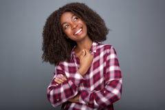 看起来去和微笑在灰色背景的方格的衬衣的可爱的黑人女孩 库存图片