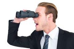 看起来双筒望远镜的生意人惊奇 免版税库存照片