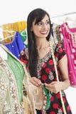 看起来可爱的印地安女性的裁缝去,当工作在成套装备时 免版税图库摄影