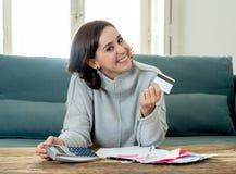 看起来可爱的年轻自由职业者的妇女满意和激动对信用卡和财务 库存照片