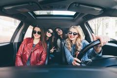 看起来四名美丽的年轻快乐的妇女愉快和嬉戏,当坐在汽车时 免版税库存图片