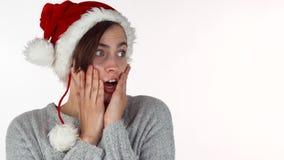 看起来圣诞节的帽子的年轻美女惊奇或冲击 影视素材
