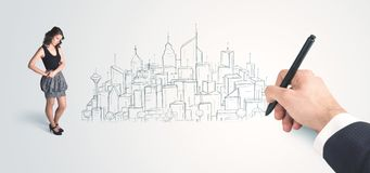 看起来在墙壁上的女实业家手头被画的城市 免版税库存照片