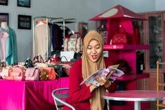 看起来在她的时尚精品店的一本年轻回教企业家开会和读书杂志的画象新的储蓄编目 免版税库存照片