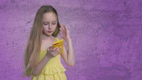 看起来在紫罗兰色墙壁背景的长发少年女孩手机 有挥动的头发的美女在风使用 影视素材