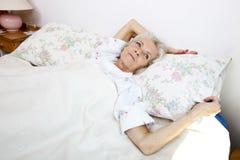 看起来大角度的观点的资深妇女去,当在家时在床上 图库摄影